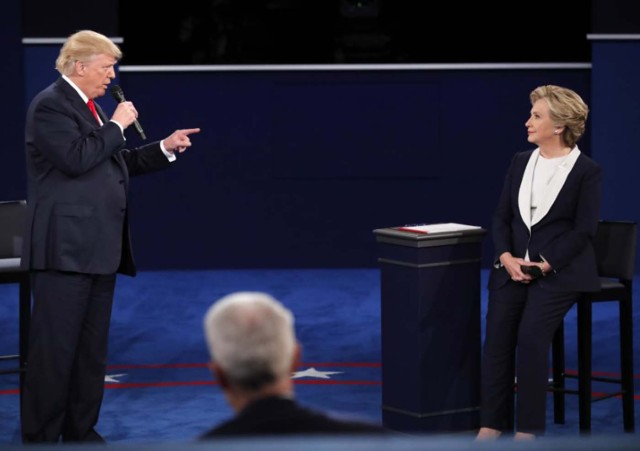 Donald Trump speaks as Hillary Clinton listens. REUTERS/Jim Young