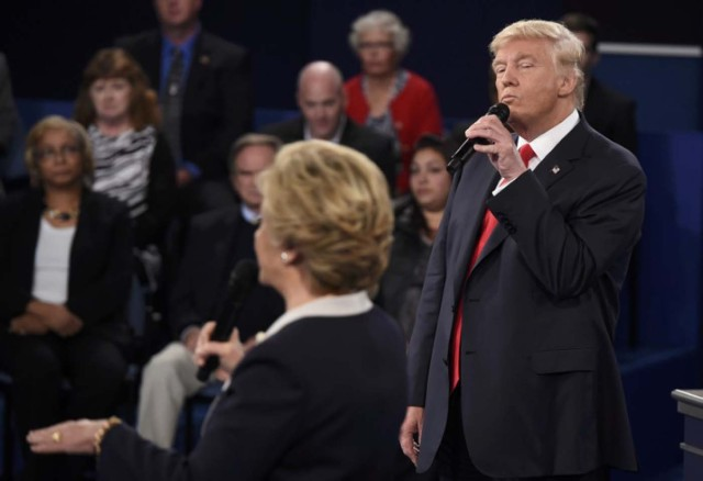 Republican U.S. presidential nominee Donald Trump listens as Democratic nominee Hillary Clinton answers a question from the audience during their presidential town hall debate at Washington University in St. Louis, Missouri, U.S., October 9, 2016. REUTERS/Saul Loeb/Pool