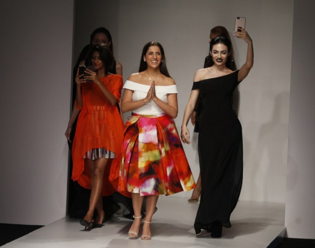 Lebanese designer Aiisha Ramadan (C) walks down the catwalk with Emirati model Rafeea Al-Hajsi (R) and other models wearing her designs the end of her show during the Arab Fashion Week in the United Arab Emirate of Dubai on October 9, 2016. Rafeea al-Hajsi fulfilled a dream by becoming the first Emirati model to strut the Arab Fashion Week catwalk after years battling social constraints. Hajsi's first appearance at a fashion show was earlier this year in France, when she modelled for Lebanese designer Ziad Nakad at Paris Fashion Week. / AFP PHOTO / KARIM SAHIB
