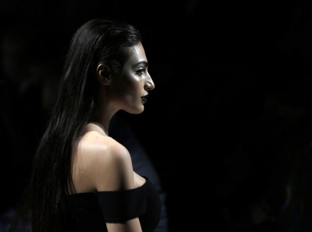 Emirati model Rafeea Al-Hajsi presents a creation by Lebanese designer Aiisha Ramadan during the Arab Fashion Week in the United Arab Emirate of Dubai on October 9, 2016. Rafeea al-Hajsi fulfilled a dream by becoming the first Emirati model to strut the Arab Fashion Week catwalk after years battling social constraints. Hajsi's first appearance at a fashion show was earlier this year in France, when she modelled for Lebanese designer Ziad Nakad at Paris Fashion Week. / AFP PHOTO / KARIM SAHIB