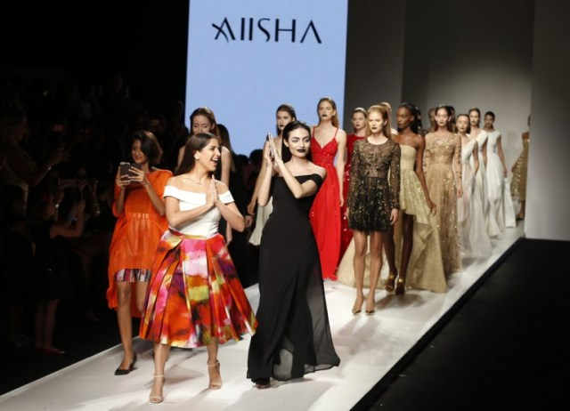 Lebanese designer Aiisha Ramadan (C) walks down the catwalk with Emirati model Rafeea Al-Hajsi (C-R) and other models wearing her designs the end of her show during the Arab Fashion Week in the United Arab Emirate of Dubai on October 9, 2016. Rafeea al-Hajsi fulfilled a dream by becoming the first Emirati model to strut the Arab Fashion Week catwalk after years battling social constraints. Hajsi's first appearance at a fashion show was earlier this year in France, when she modelled for Lebanese designer Ziad Nakad at Paris Fashion Week. / AFP PHOTO / KARIM SAHIB
