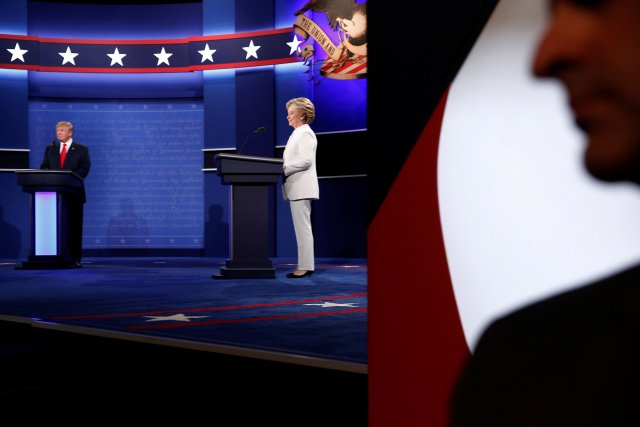 A Secret Service agent stands near the stage as Republican U.S. presidential nominee Donald Trump (L) and Democratic U.S. presidential nominee Hillary Clinton (C) begin their third and final 2016 presidential campaign debate at UNLV in Las Vegas, Nevada, U.S., October 19, 2016. REUTERS/Jonathan Ernst