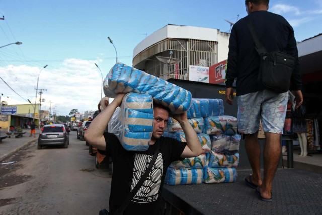ACOMPAÑA CRÓNICA: BRASIL VENEZUELA - BRA08. PACARAIMA (BRASIL), 24/10/2016.- Fotografía del 21 de octubre de 2016, de un grupo de venezolanos en la ciudad de Pacaraima, una empobrecida y pequeña ciudad del norte de Brasil, que se ha convertido en uno de las últimos horizontes en que los venezolanos consiguen la comida y los productos básicos que escasean en su país. Según distintas fuentes consultadas por Efe en esta ciudad de la frontera entre Brasil y Venezuela, entre 1.000 y 1.500 venezolanos cruzan cada fin de semana la línea divisoria, compran alimentos y regresan a su país. EFE / Marcelo Sayão
