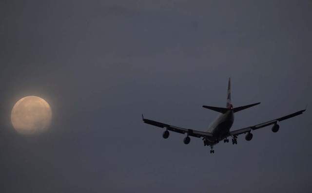"""A passenger aircraft makes it's landing approach to Heathrow airport in front of a """"super moon"""" at dawn in west London, Britain, October 17, 2016. REUTERS/Toby Melville"""