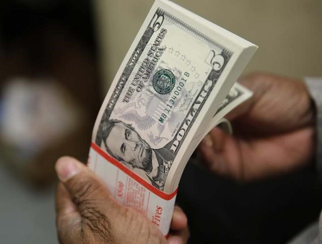 Un empleado revisando billetes de 5 dólares en la Casa de la Moneda de los Estados Unidos en Washington, mar 26, 2015.El dólar se disparó el miércoles a su mayor nivel en 14 años contra una cesta de monedas y tocó un máximo de un año frente al euro, en momentos en que los grandes bancos e inversores empezaron a debatir la posibilidad de otra alza hasta alcanzar la paridad con la divisa única del bloque.  REUTERS/Gary Cameron/File Photo