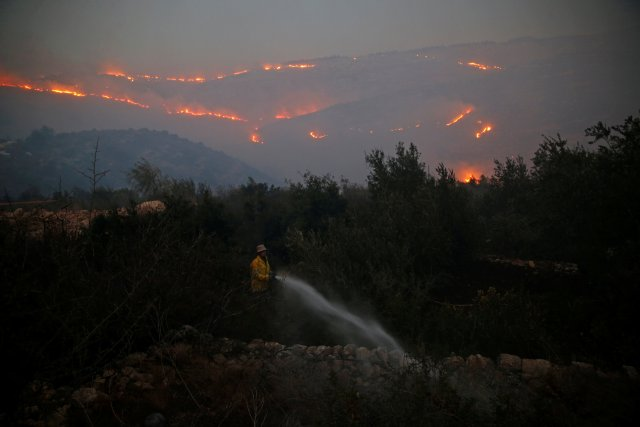 A firefighter sprays water around a house in Nataf as wildfire burns on the hills and mountains around it, outside Jerusalem November 25, 2016.  REUTERS/Ammar Awad     TPX IMAGES OF THE DAY