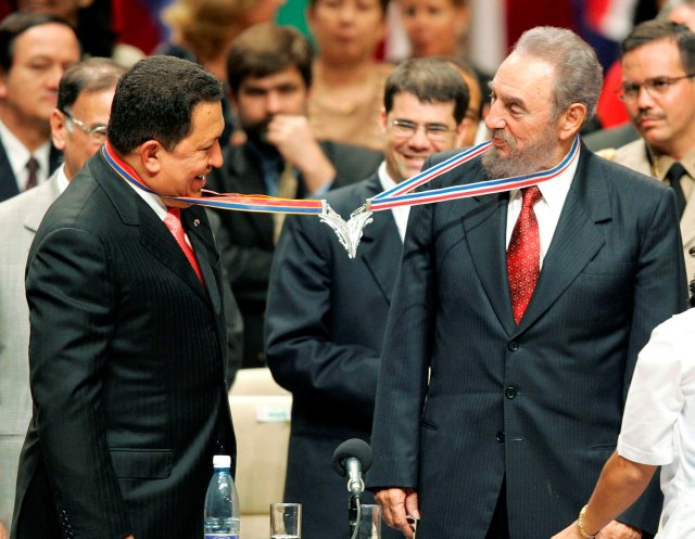 Venezuela's President Hugo Chavez (L) and his Cuban counterpart Fidel Castro joke after joining their medallions, given by medical graduates, at Havana's Karl Marx theatre, in this August 20, 2005 file photo.  REUTERS/Claudia Daut/File Photo