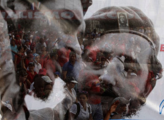 People are seen through a poster with a picture of Cuba's former leader Fidel Castro and late Argentine revolution leader Che Guevara (L) during the May Day parade in Havana's Revolution Square in this May 1, 2013 file photo. REUTERS/Desmond Boylan/File Photo