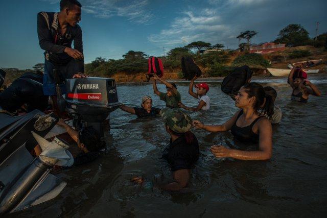 Emigrantes venezolanos embarcando en un bote de contrabandistas que los llevará hasta la isla de Curazao. Credit Meridith Kohut para The New York Times