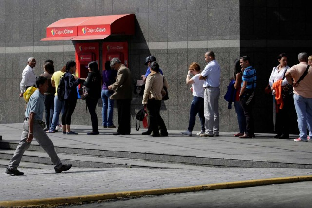 People line up to withdraw cash from an automated teller machine (ATM) outside a Banco de Venezuela branch in Caracas, Venezuela November 23, 2016. Picture taken November 23, 2016. REUTERS/Marco Bello
