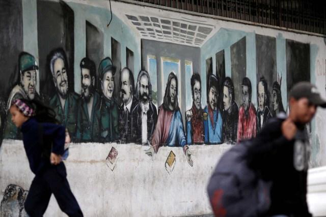 People pass next to a mural depicting the communist leaders at the 23 Enero neighbourhood in Caracas, Venezuela, November 30, 2016. REUTERS/Ueslei Marcelino