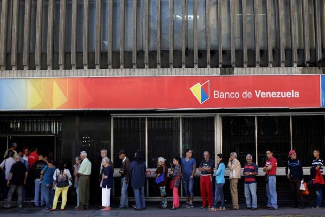 People line up to withdraw cash from a Banco de Venezuela branch in Caracas, Venezuela December 2, 2016. REUTERS/Ueslei Marcelino