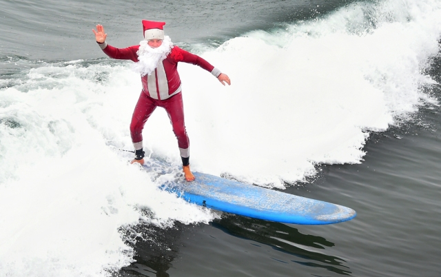 Surfing Santa, Michael Pless, waves while riding a wave at Seal Beach, California, on December 10, 2016, where he runs a surfing school and has every December since in 1990's gone out to surf in his Santa Claus outfit. / AFP PHOTO / Frederic J. BROWN