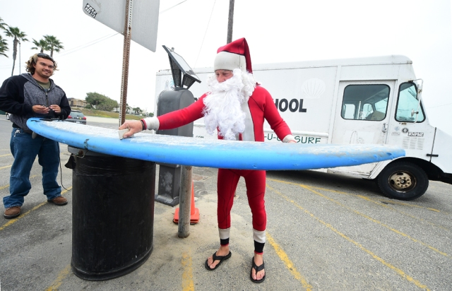 Surfing Santa, Michael Pless, waxes his board before catching a wave at Seal Beach, California on December 10, 2016, where he runs a surfing school and has every December since in 1990's gone out to surf in his Santa Claus outfit. / AFP PHOTO / Frederic J. BROWN
