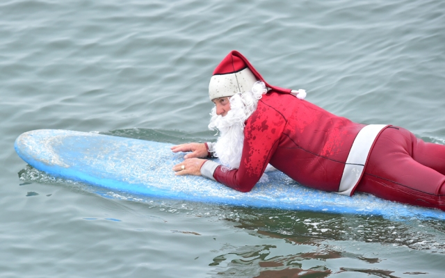 Surfing Santa, Michael Pless, lays on his board making his way out to catch a wave at Seal Beach, California on December 10, 2016, where he runs a surfing school and has every December since in 1990's gone out to surf in his Santa Claus outfit. / AFP PHOTO / Frederic J. BROWN