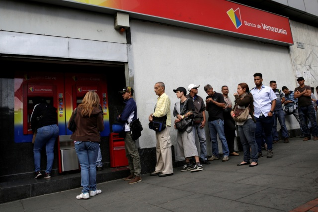 People line up to withdraw cash from an automated teller machine (ATM) outside a Banco de Venezuela branch in Caracas, Venezuela December 12, 2016. REUTERS/Marco Bello
