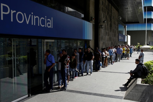 People line up to withdraw cash from an automated teller machine (ATM) outside a Banco Provincial branch in Caracas, Venezuela December 12, 2016. REUTERS/Marco Bello