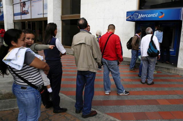 People line up to withdraw cash from an automated teller machine (ATM) outside a Banco Mercantil branch in Caracas, Venezuela December 12, 2016. REUTERS/Marco Bello