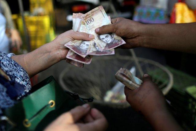A cashier receives Venezuelan bolivar notes from a customer at a street market in downtown Caracas, Venezuela, December 12, 2016. REUTERS/Ueslei Marcelino