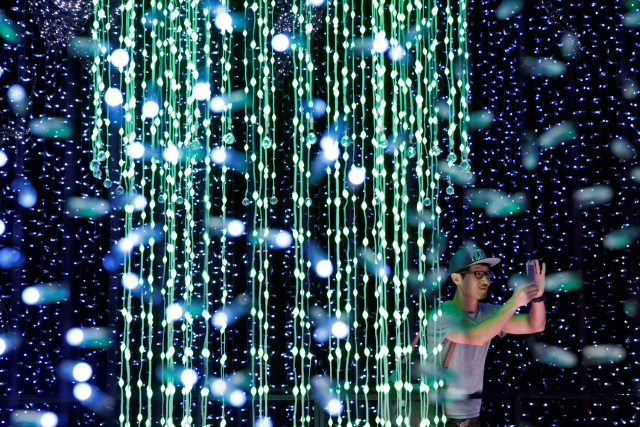 A man tours a Christmas attraction featuring a display of more than 800,000 light bulbs in Universal Studios Singapore December 12, 2016. REUTERS/Edgar Su