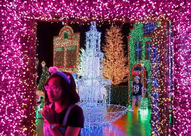 People tour a Christmas attraction featuring a display of more than 800,000 light bulbs in Universal Studios Singapore December 12, 2016. REUTERS/Edgar Su