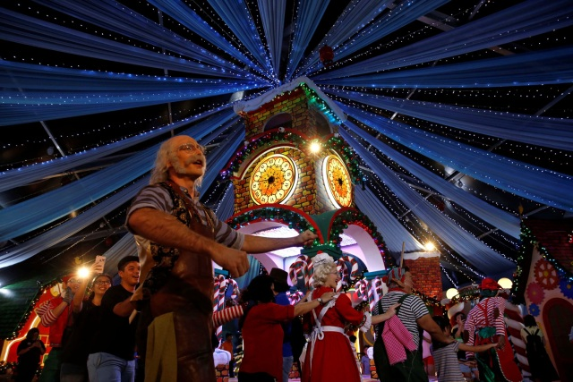 People dance with performers at a Christmas attraction in Universal Studios Singapore December 12, 2016. REUTERS/Edgar Su