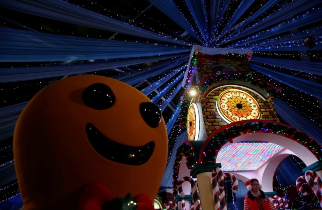A performer dressed as a gingerbread man dances with people at a Christmas attraction in Universal Studios Singapore December 12, 2016. REUTERS/Edgar Su