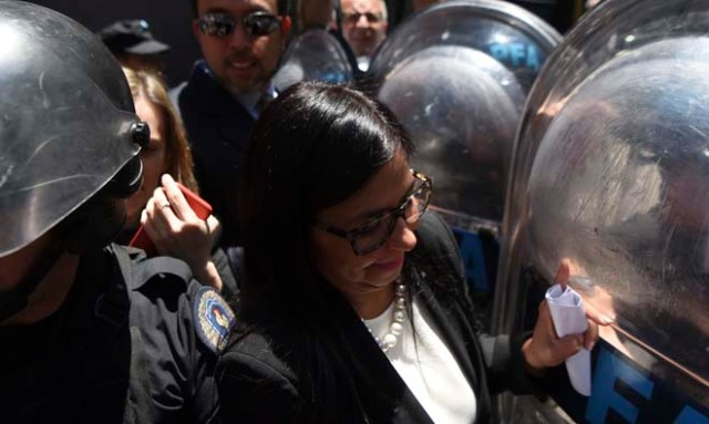 Venezuela's Foreign Minister Delcy Rodriguez, is blocked by riot police officers before entering the Argentine Foreign Ministry in Buenos Aires during a meeting among Mercosur's ministers where Venezuela was not invited, on December 14, 2016. Mercosur's foreign ministers debate on Venezuela's suspension from the group after accusations that the leftist government in Caracas failed to meet democratic and trade standards. / AFP PHOTO / EITAN ABRAMOVICH