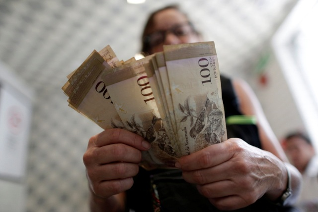 A cashier counts Venezuelan bolivar notes inside a restaurant in downtown Caracas, Venezuela, December 12, 2016. REUTERS/Ueslei Marcelino