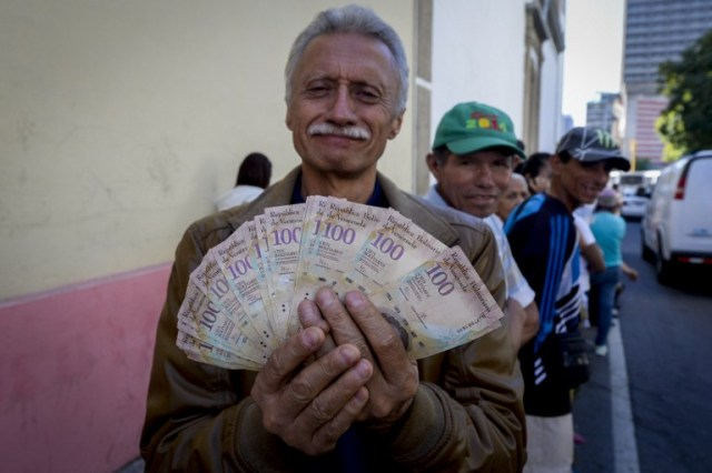 A man shows 100 Bolivar notes whilst queuing outside Venezuela's Central Bank (BCV) in Caracas in an attempt to change them, on December 16, 2016. Venezuelans lined up to deposit 100-unit banknotes before they turned worthless, but replacement bills had yet to arrive, increasing the cash chaos in the country with the world's highest inflation. Venezuelans are stuck in currency limbo after President Nicolas Maduro ordered the 100-bolivar note -- the largest denomination, currently worth about three US cents -- removed from circulation in 72 hours. / AFP PHOTO / FEDERICO PARRA