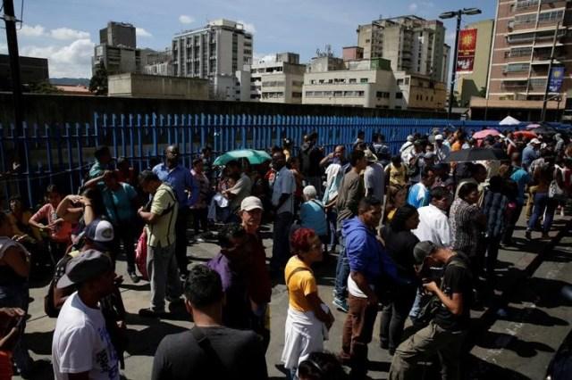 Personas en fila para depositar billetes de 100 bolívares cerca del Banco Central de Venezuela, dic 16, 2016. Miles de venezolanos protestaban en varias ciudades, frustrados al no poder canjear sus existencias de billetes de 100 bolívares, que desde el viernes perdieron todo su valor comercial. REUTERS/Marco Bello
