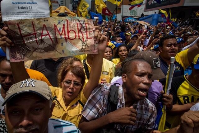 """CAR25. CARACAS (VENEZUELA) 14/05/2016.- Una manifestante sostiene un letrero con la palabra """"Hambre"""" en una protesta contra el Gobierno venezolano hoy, sábado 14 de mayo del 2016, en Caracas (Venezuela). Centenares de opositores se concentraron hoy en una de las calles de la capital para exigir a las autoridades electorales que den celeridad a la solicitud de la activación de un referendo revocatorio que permita terminar con el mandato del presidente de Venezuela, el chavista Nicolás Ma duro. EFE/MIGUEL GUTIERREZ"""