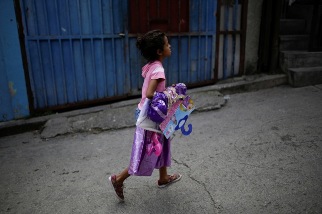 A girl walks with a costume received during a toy distribution program with Miguel Pizarro, deputy of the Venezuelan coalition of opposition parties (MUD), at the slum of Petare in Caracas, Venezuela December 20, 2016. Picture taken December 20, 2016. REUTERS/Marco Bello