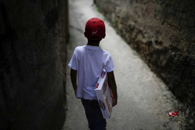 A boy walks with a toy received during toy distribution program with Miguel Pizarro, deputy of the Venezuelan coalition of opposition parties (MUD), in an alley at the slum of Petare in Caracas, Venezuela December 20, 2016. Picture taken December 20, 2016. REUTERS/Marco Bello