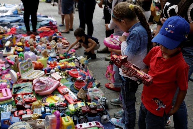 Children look at second-hand toys at a street market in the slum of Catia in Caracas, Venezuela December 21, 2016. Picture taken December 21, 2016. REUTERS/Marco Bello