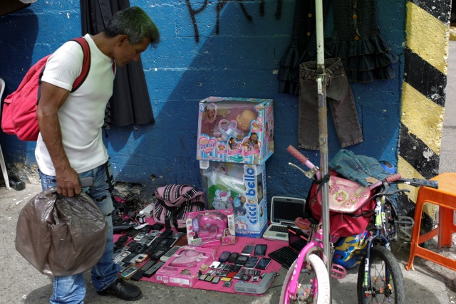 A man looks at second-hand toys at a street market in the slum of Catia in Caracas, Venezuela December 21, 2016. Picture taken December 21, 2016. REUTERS/Marco Bello