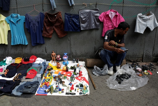 A vendor sits next to second-hand toys and clothes at a street market in the slum of Catia in Caracas, Venezuela December 21, 2016. Picture taken December 21, 2016. REUTERS/Marco Bello