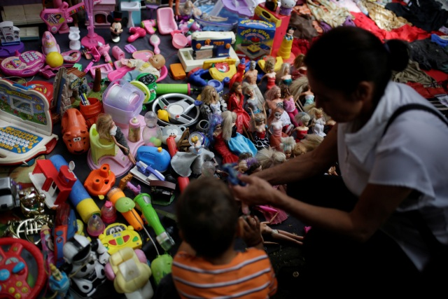 People look at second-hand toys at a street market in the slum of Catia in Caracas, Venezuela December 21, 2016. Picture taken December 21, 2016. REUTERS/Marco Bello