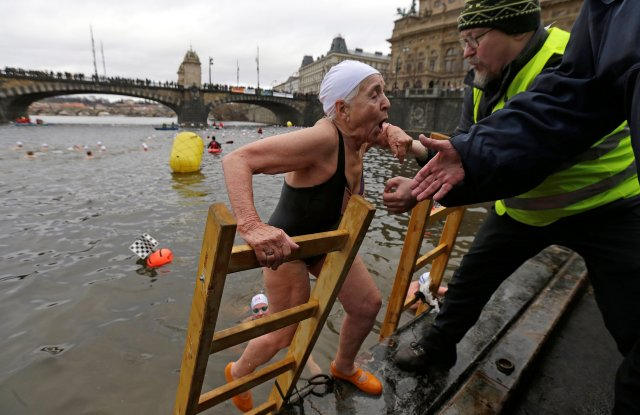 A swimmer is helped out of the Vltava river after the annual Christmas winter swimming competition in Prague, Czech Republic, December 26, 2016. REUTERS/David W Cerny