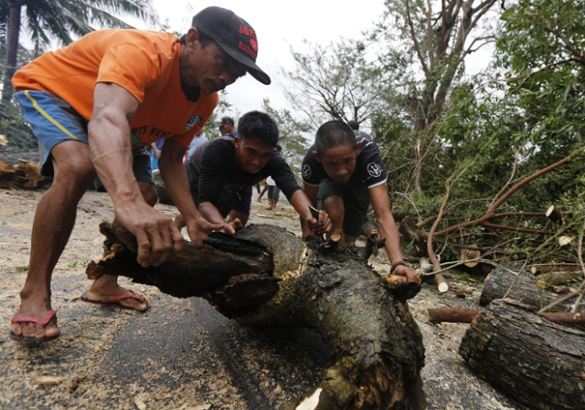 FRM101. Milaor (Philippines), 25/12/2016.- Filipino villagers clear debris from a road in the typhoon-hit town of Milaor, Camarines Sur, Philippines, 26 December 2016. According to Office of Civil Defense (OCD) reports on 26 December, hundreds of thousands of villagers spent their Christmas day in evacuation centers in Bicol region, many flights were cancelled at Manila's internatioanal airport, and scores of sea vessels have reportedly sunk as Typhoon Nock-ten brought howling winds and strong rains in central Philippines. (Filipinas) EFE/EPA/EUGENIO LORETO