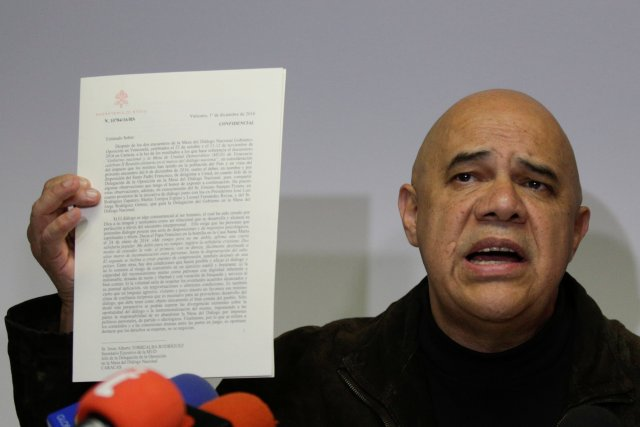 Jesus Torrealba, secretary of the MUD, holds a letter from Vatican Secretary of State Cardinal Pietro Parolin as he talks to the media during a news conference in Caracas
