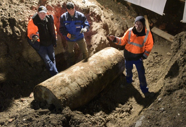 The bomb disposal team stand next to the World War II bomb they made safe in Augsburg, southern Germany, during a mass evacuation on December 25, 2016. Around 54,000 residents are being evacuated from their homes after the discovery of a bomb dating from World War II, local authorities said. / AFP PHOTO / dpa / Stefan Puchner / Germany OUT