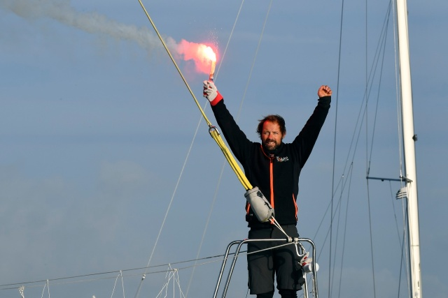 "French skipper Thomas Coville holds a burning flare onboard his ""Sodebo Ultim'"" multihull as he arrives in the port of Brest, western France, on December 26, 2016, after beating the record in solo non-stop round the world sailing. Coville, 48, slashed eight days off the record when he ended an astonishing solo non-stop circumnavigation of the World on his 31m maxi trimaran on December 25, 2016, in just 49 days, 3 hours, 7mins and 38secs. / AFP PHOTO / Damien MEYER"