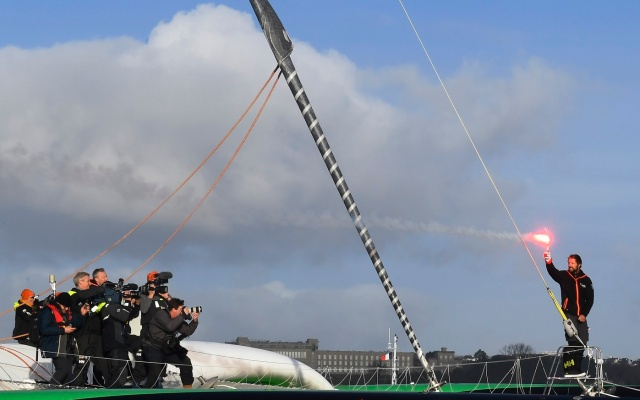 "French skipper Thomas Coville (R) holds a flare as photographers take pictures onboard his ""Sodebo Ultim'"" multihull as he arrives in the port of Brest, western France, on December 26, 2016, after beating the record in solo non-stop round the world sailing. Coville, 48, slashed eight days off the record when he ended an astonishing solo non-stop circumnavigation of the World on his 31m maxi trimaran on December 25, 2016, in just 49 days, 3 hours, 7mins and 38secs.  / AFP PHOTO / Damien MEYER"
