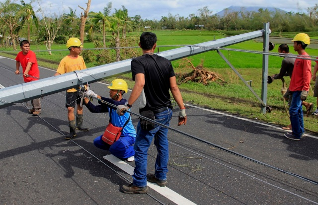 Workers check downed electric posts on the national road after typhoon Nock-Ten made landfall in Nabua, Camarines Sur on December 26, 2016. Typhoon Nock-Ten, which made landfall on the eastern island province of Catanduanes on December 25, is forecast to move westward towards the country's heartland, packing winds of 215 kilometres (134 miles) per hour. / AFP PHOTO / Charism SAYAT
