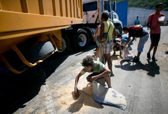 En esta imagen del 14 de noviembre de 2016, un joven utiliza una funda de almohada para recoger arroz del pavimento caído de un camión de mercancías que espera para entrar en Puerto Cabello, Venezuela. (AP Foto/Ariana Cubillos)