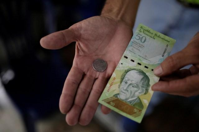 Un comerciante sostiene una moneda de 50 bolívares y un billete de 50 bolívares para esta fotografía tomada en un puesto callejero en el centro de Caracas, Venezuela