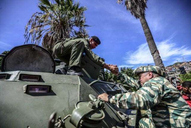 Venezuelan lawmaker Diosdado Cabello (R) mounts in an armoured tank during a demonstration in Caracas on January 14, 2017. / AFP PHOTO / JUAN BARRETO