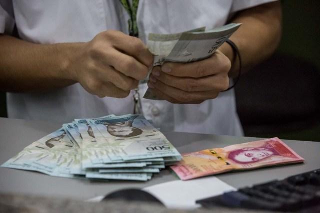 """CAR01. CARACAS (VENEZUELA), 16/01/2017.- Trabajadores de un banco manipulan billetes del nuevo cono monetario hoy 16 de enero de 2017, en Caracas (Venezuela). Los billetes de 500, 5.000 y 20.000 bolívares, tres de las seis piezas que conforman el nuevo cono monetario, comenzaron a circular hoy en Venezuela tal y como lo aseguró ayer el presidente, Nicolás Maduro, y un mes más tarde de lo previsto inicialmente debido a un """"sabotaje internacional"""". EFE/Miguel Gutiérrez"""