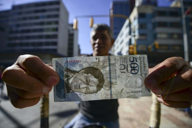 A street coffee vendor shows a new 500-Bolivar-note (74 cents of US dollar) in Caracas on January 16, 2017. A new family of currency will progressively come into circulation in the South American country that has the highest inflation rate in the world, which IMF forecasts say could soon hit 475 percent. / AFP PHOTO / JUAN BARRETO